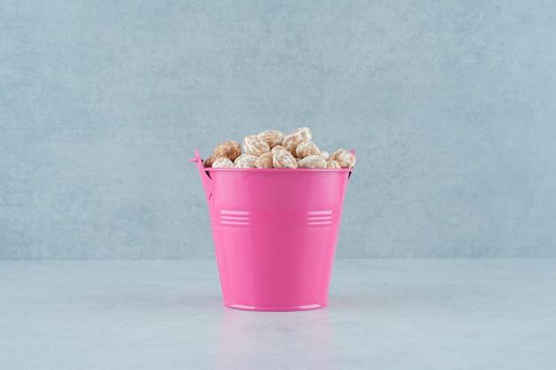 白い背景の上の甘いおいしいジンジャーブレッドでいっぱいのピンクのバケツ。高品質の写真
