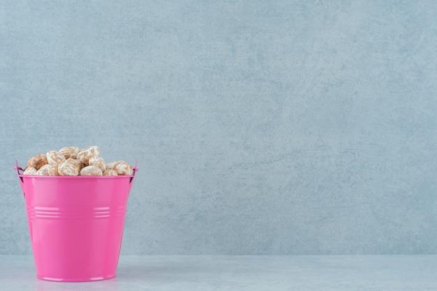 흰색 표면에 달콤한 맛있는 진저 브레드의 전체 분홍색 양동이