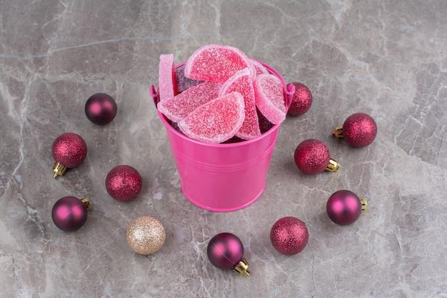大理石の背景に赤いクリスマスボールと甘いマーマレードでいっぱいのピンクのバケツ。