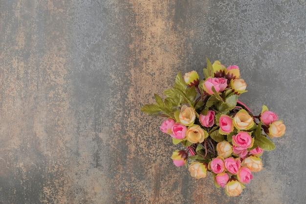 Розовое ведро с букетом цветов на мраморной поверхности.