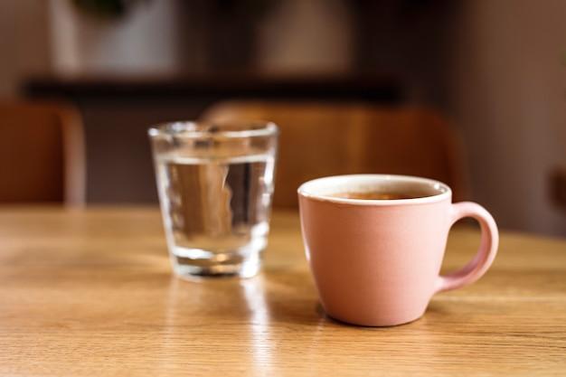 Розовая керамическая чашка горячего черного кофе на деревянном столе и стакан воды, кафе, деревянный стол
