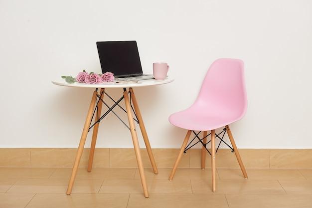 ピンクの椅子と壁に白いテーブル。テーブルの上には、ラップトップ、グラス、カップ、バラの花束があります。スタジオのインテリアや職場。