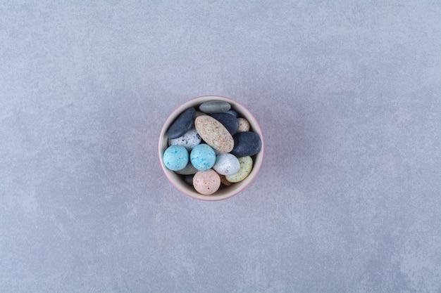 형형색색의 콩사탕이 가득한 핑크색 컵. 고품질 사진
