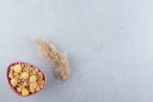 회색 표면에 맛있는 건강 시리얼의 분홍색 깊은 그릇