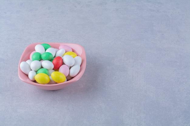 회색 배경에 다채로운 콩 사탕으로 가득 찬 분홍색 깊은 접시. 고품질 사진