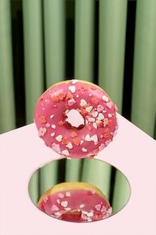 ピンクのドーナツが緑のカーテンを背景に鏡に落ちます。