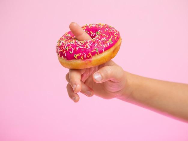 Розовый пончик, надетый на палец ребенка, повеселитесь с едой, сладким клубничным пончиком на розовом му