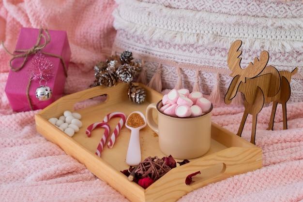 Розовый домашний уголок с одеялом, подушкой, рождественским подарком и украшениями. деревянный поднос с керамической чашкой с зефиром. концепция уютных праздников и нового года.