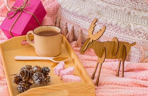 Розовый домашний уголок с одеялом, подушкой и рождественским подарком. деревянный поднос с горячим шоколадом в керамической кружке. концепция уютных праздников и нового года.