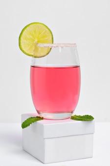 Бокал для коктейля розовая леди, украшенный лимонным фотогарафадо на белом фоне