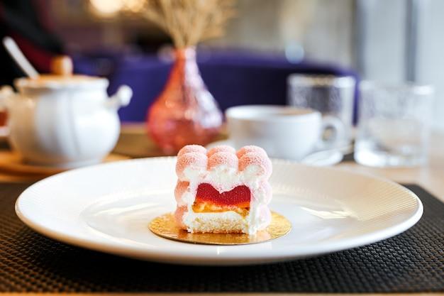 Розовый муссовый торт с малиновым желе и банановой начинкой на белой тарелке в ресторане, чашка кофе