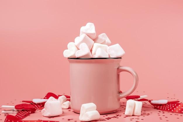 ピンクのマグカップが横になっていて、マシュマロがハートの形で散らばっています