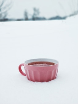 雪の降る冬の野原で熱いラズベリーティーとピンクのマグカップ。寒い冬にはジャム入りのお茶が温まります。