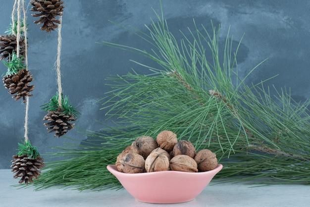Розовая тарелка с грецкими орехами и рождественскими шишками на мраморном фоне. фото высокого качества