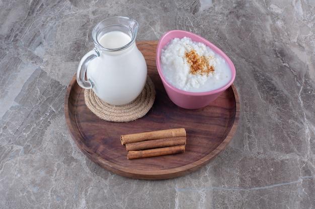 Розовая тарелка здоровой овсяной каши со стеклянным кувшином молока и палочками корицы на деревянной доске.