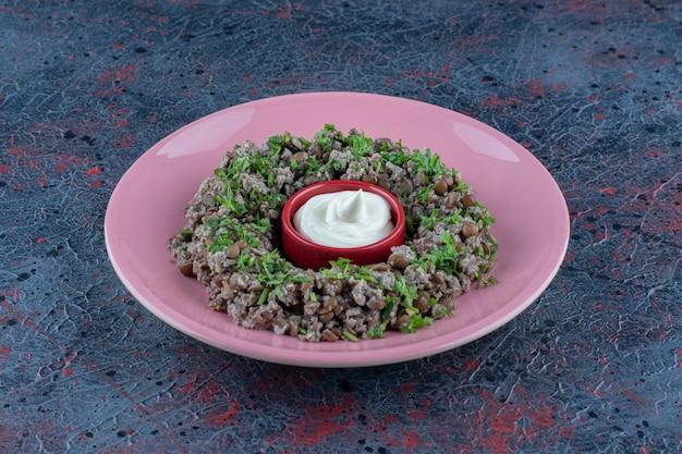 완두콩과 허브를 곁들인 다진 고기의 분홍색 접시.