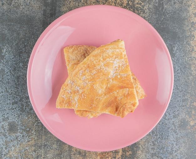 수제 트라이앵글 파이 2 개와 설탕을 넣은 분홍색 접시