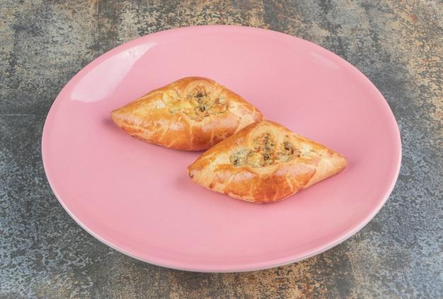 自家製の三角形のパイが2つ付いたピンクのプレート