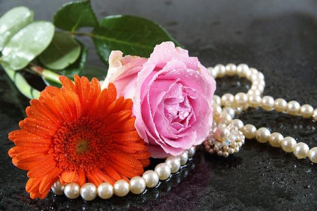 ピンクのバラとオレンジ色のガーベラが暗い花崗岩の表面に横たわっています