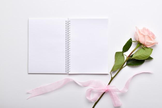 開いたノートの横にリボン付きのピンクのバラがあります。ロマンス。詩とインスピレーション。