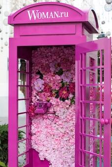 화사한 꽃으로 장식된 핑크색 공중전화 부스. 우아한 웨딩 포토존