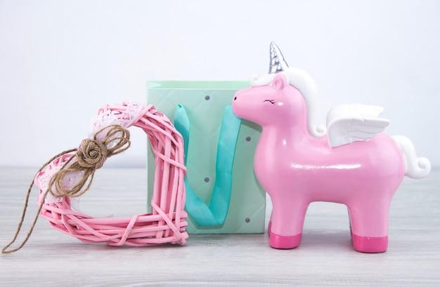Розовый единорог стоит рядом с подарочным пакетом и игрушечным сердечком. милый подарок девушке.
