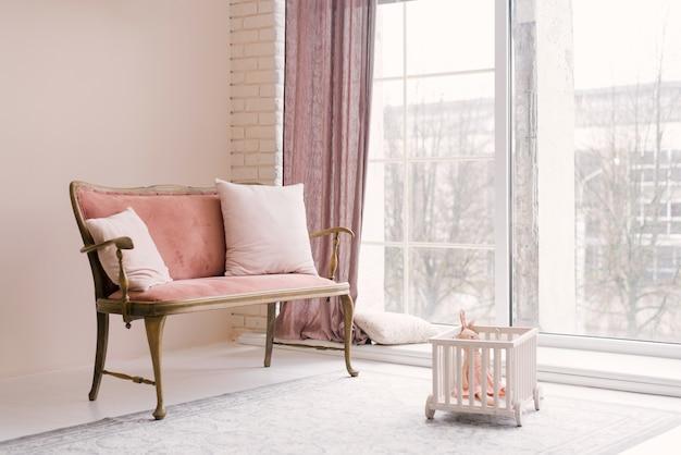 Розовый винтажный диван с подушками стоит у окна в гостиной или детской комнате
