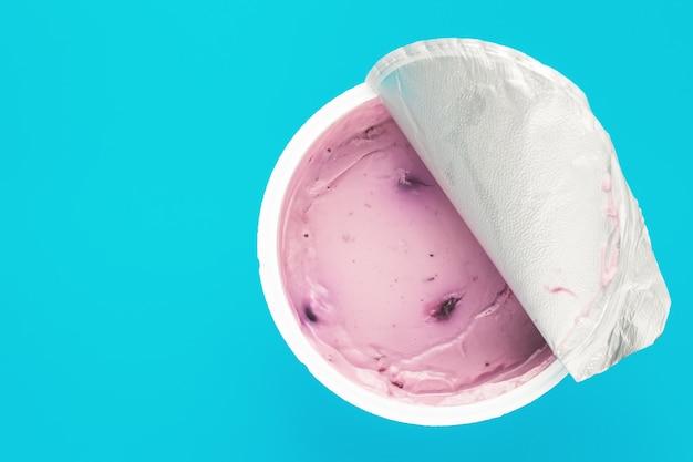 青色の背景に開いているプラスチックカップにブルーベリーとピンクヨーグルト。トップビュー、テキストスペース。