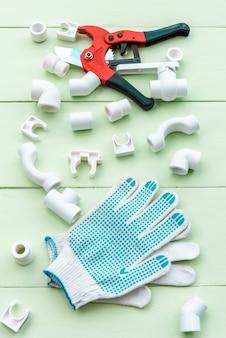 Труборез и ремонтные перчатки лежат на деревянном столе вместе с пластиковыми трубами.