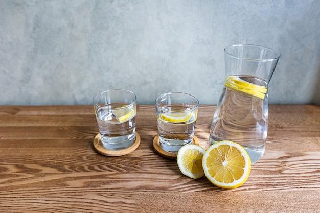 Кувшин и стаканы чистой воды с лимоном. концепция здорового образа жизни