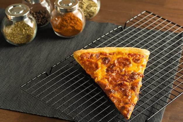 Пицца с начинкой пепперони на охлаждающей решетке поставить на салфетку из черной ткани.