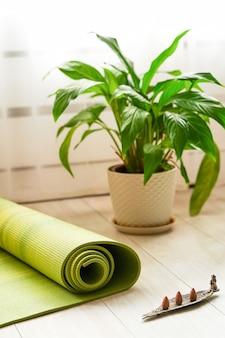 自宅でヨガを練習する場所ヨガマットとお香が瞑想とリラクゼーションのためにすべてを貼り付けます