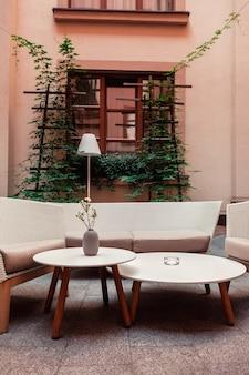 Место для отдыха с креслами и диваном из соломы во дворе на фоне дома.