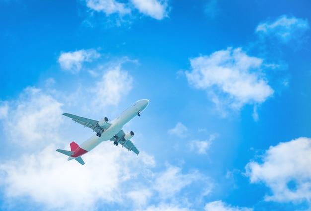 白い雲と青い空を飛んでいる飛行機