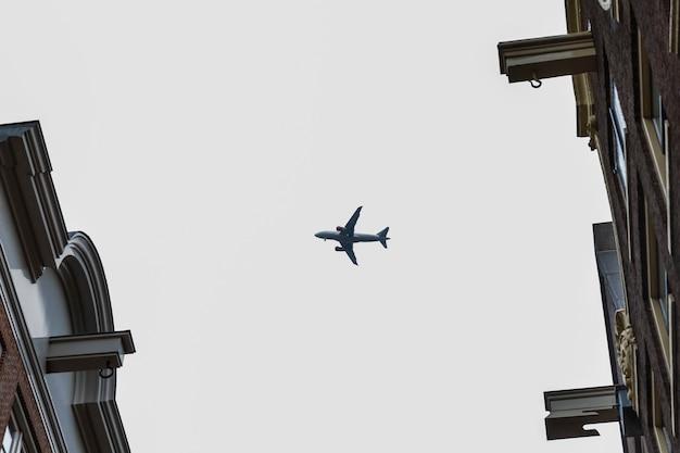 家の間を飛んでいる曇り空の飛行機。テキスト用のスペース。
