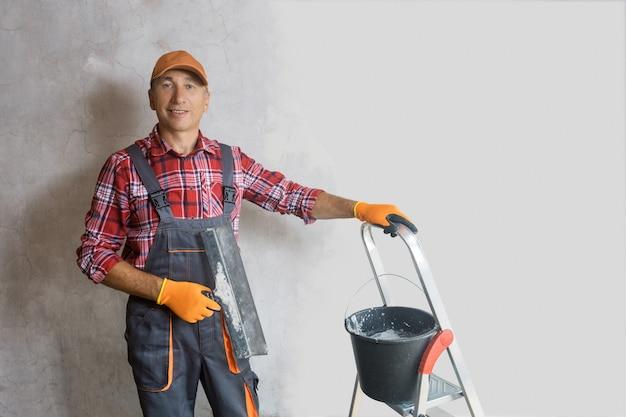 미장공, 벽 앞에 흙손을 펴고 있는 건축업자. 개별 사람들이 개조하는 집의 개념입니다.