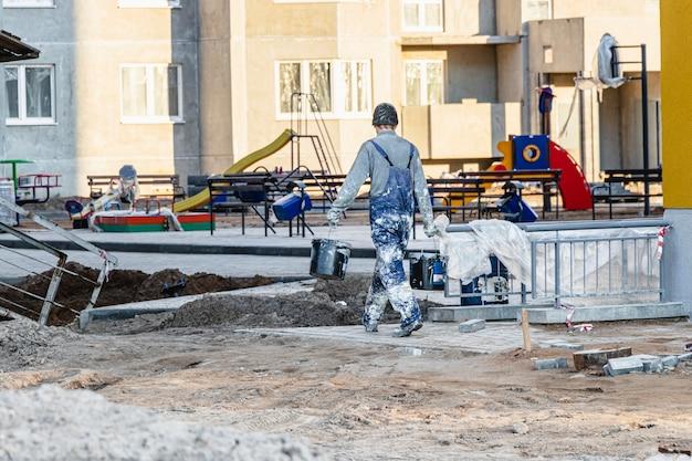건설 현장에서 더러운 작업복을 입은 미장공이나 화가. 남성 작업자가 도구를 운반합니다.
