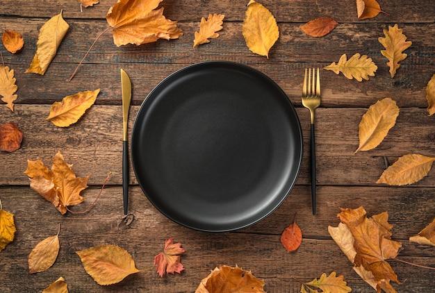 Тарелка, нож, вилка и осенние листья на деревянном фоне