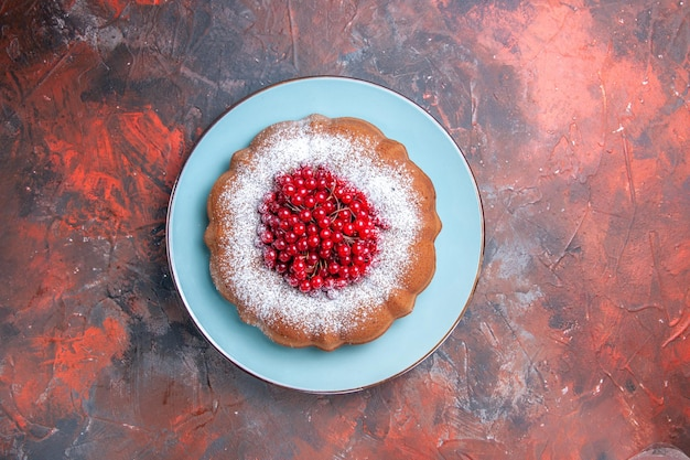 빨간색-파란색 테이블에 붉은 건포도가 있는 케이크의 접시 파란색 접시