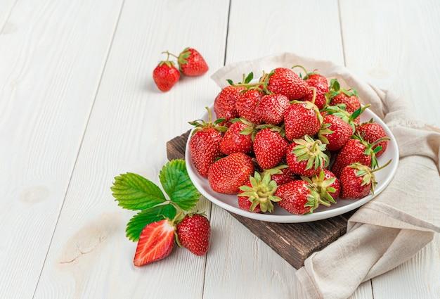 밝은 배경의 나무 스탠드에 익은 딸기로 가득 찬 접시