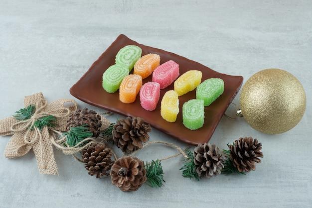 白い背景の上のマーマルドと大きなクリスマスボールでいっぱいのプレート。高品質の写真