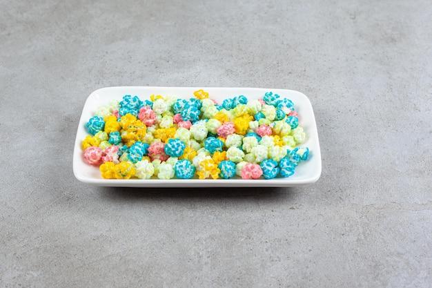 Тарелка полная конфет попкорна на мраморном фоне. фото высокого качества