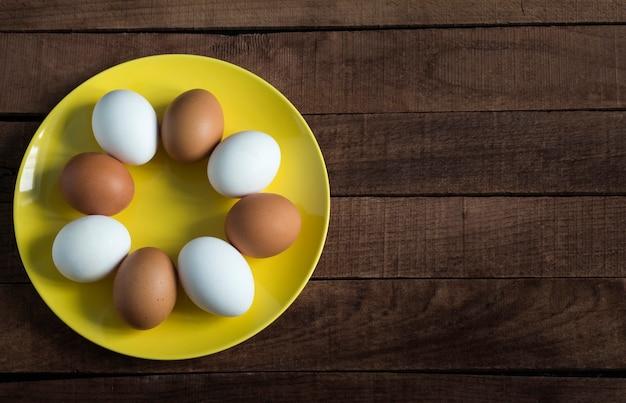 Тарелка, полная сырых цельных куриных яиц для приготовления свежих домашних блюд с копией пространства.
