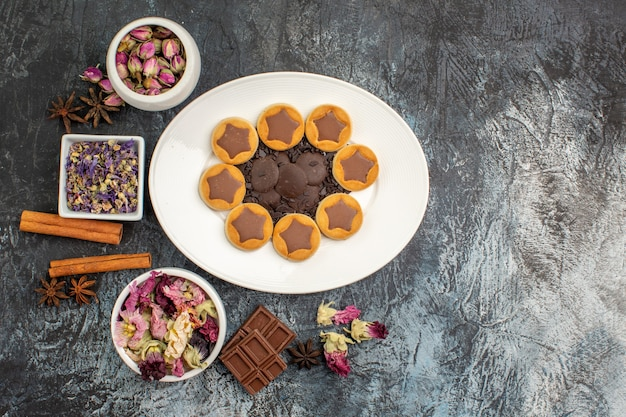 灰色の地面にドライフラワーとチョコレートバーのさまざまなボウルと各種クッキーのプレート