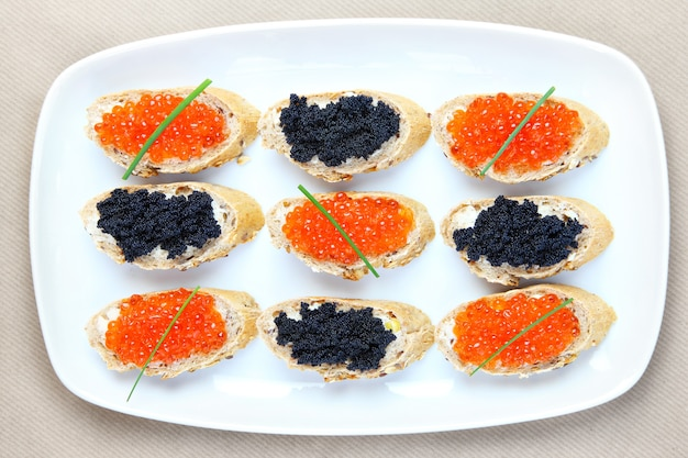 Тарелка бутербродов с черной и красной икрой