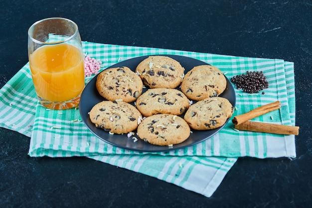 シナモンと暗いテーブルの上のチョコレートチップクッキーとオレンジジュースのガラスのプレート
