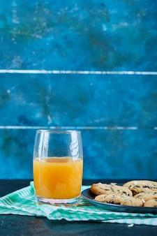 暗いテーブルの上のチョコレートチップクッキーのプレートとオレンジジュースのガラス