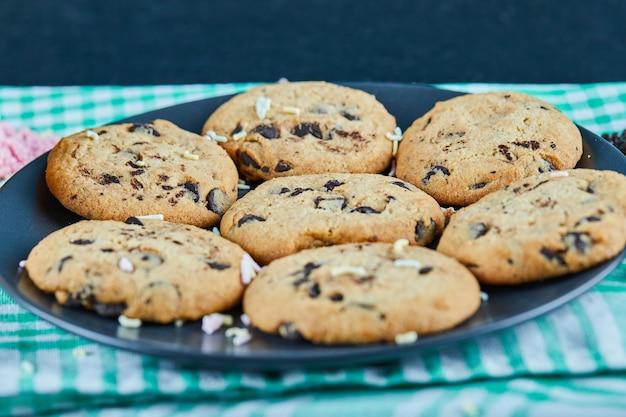 暗いテーブルの上のチョコレートチップクッキーのプレート