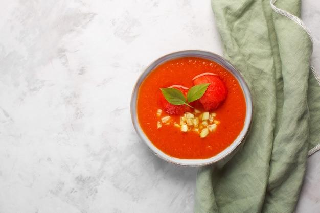 차가운 가스파초 퓌레 수프 한 접시. 올리브 타월과 회색 콘크리트 배경에 균형 잡힌 토마토, 후추, 타바스코 소스의 전통적인 스페인 요리