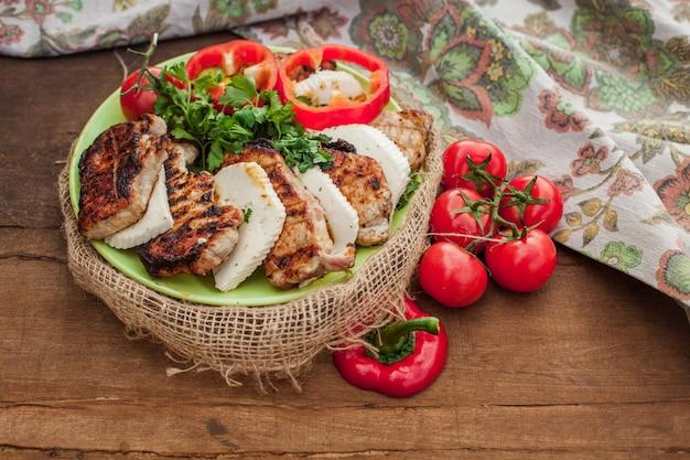 木製のテーブルの上に調理された肉、チーズ、赤野菜のプレート。ヴィンテージの装飾が施されたテキスタイルテーブルクロスの近く